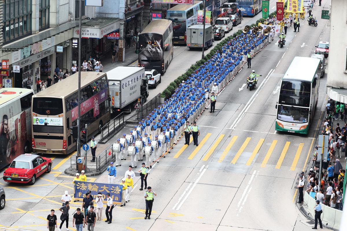 2018年10月1日法輪功反迫害大遊行,天國樂團整齊的隊伍和雄壯的奏樂,引來市民遊客夾道觀看,紛紛拍照。(李逸/大紀元)