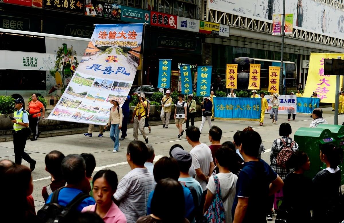 2018年10月1日「國殤日」,香港法輪功學員舉行盛大的反迫害集會遊行。壯觀的遊行隊伍經過旺角彌敦道,吸引市民遊客夾道觀看。(宋碧龍/大紀元)