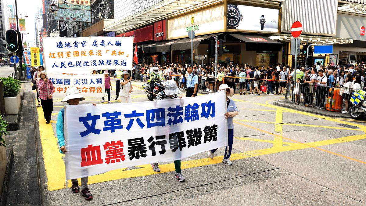 2018年10月1日「國殤日」,香港法輪功學員舉行盛大的反迫害集會遊行。壯觀的遊行隊伍經過旺角彌敦道,吸引市民遊客夾道觀看。(李拔/大紀元)