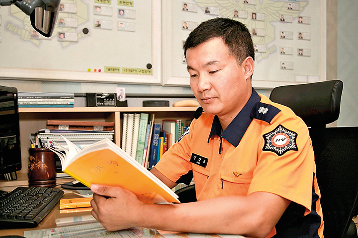 韓國仁川消防隊長辛相教在閱讀法輪大法經書。(明慧網)