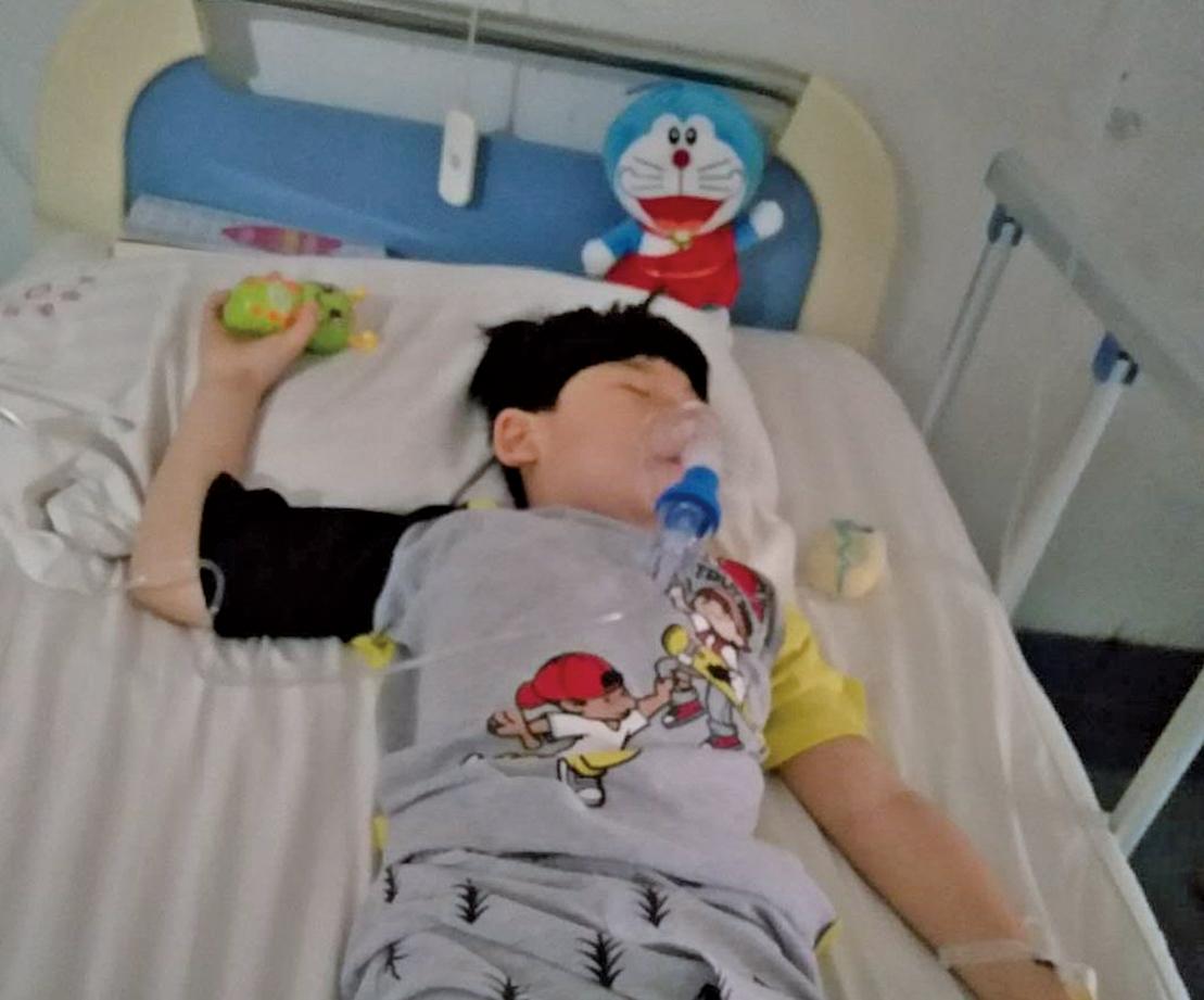 王金鳳兒子因接種毒疫苗而致腦損傷,智商偏低、無法正常走路。(受訪者提供)