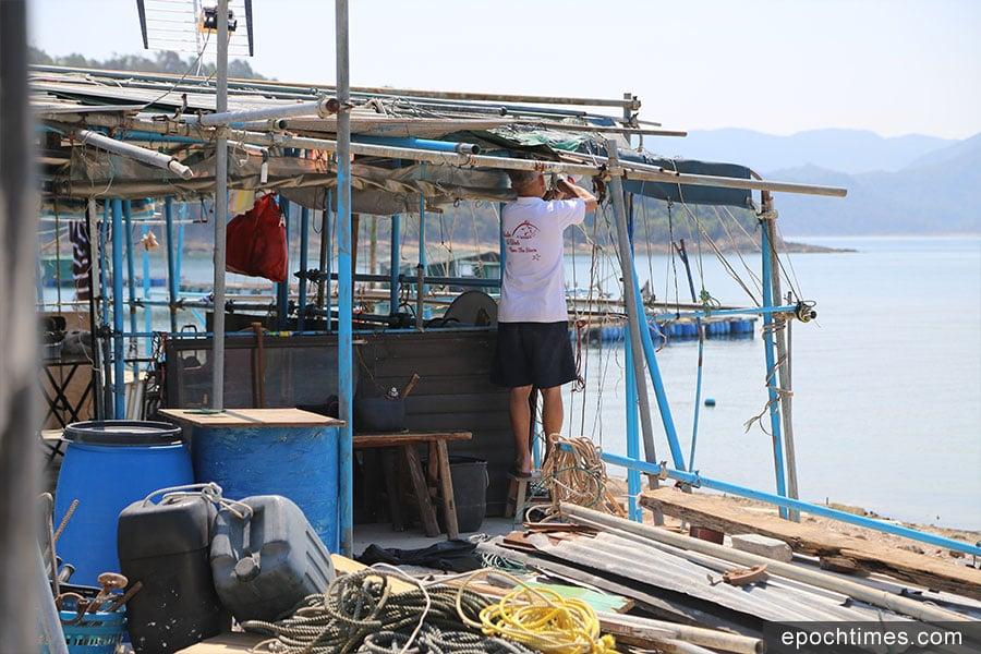 部份吉澳漁民村原居民在風災後,返回村中清理及維修房屋。圖為一名當地村民正在維修房屋。(陳仲明/大紀元)