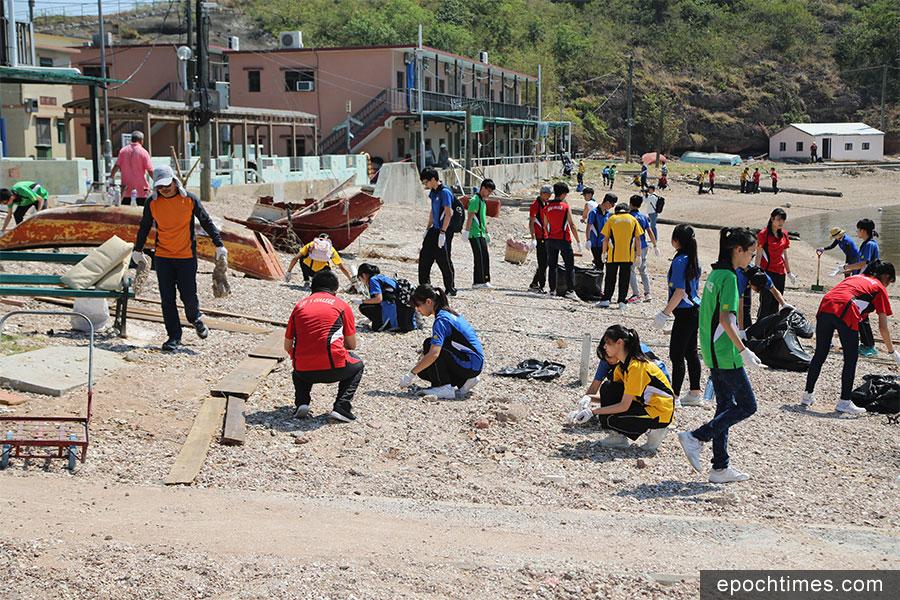 獅子會中學學生頂著炎炎烈日在灼熱的沙灘上清理垃圾。(陳仲明/大紀元)