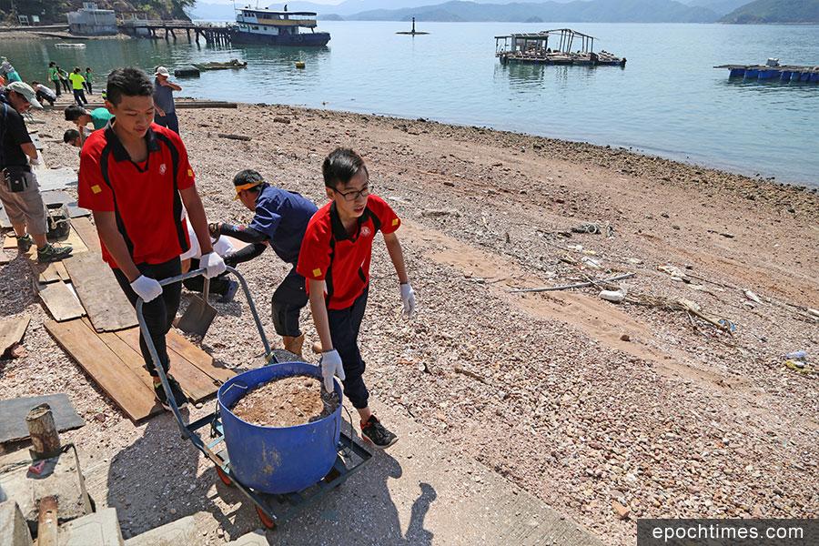 學生們幫助清理泥沙,疏通水渠。(陳仲明/大紀元)
