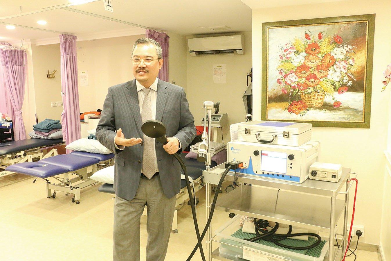 葉衛民醫生展示放在頭部能產生微弱電波,幫助刺激腦細胞活動及改善訊息傳遞的電磁線圈。(江夏/大紀元)