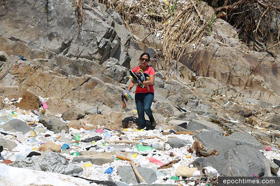 面對眼前一片汪洋般的塑膠垃圾堆,Kitti仍然堅持繼續清理工作。(陳仲明/大紀元)