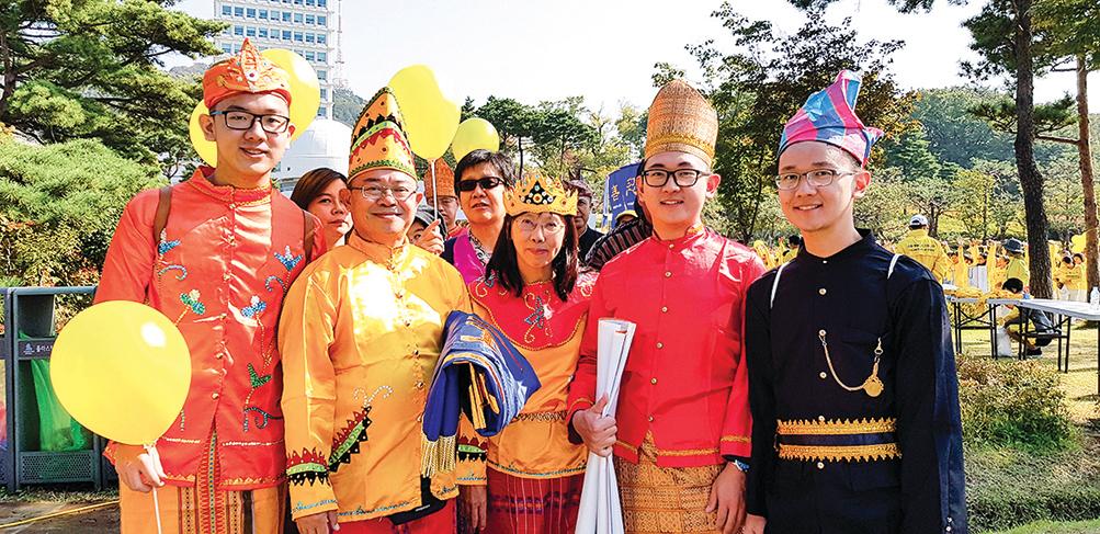 印尼的法輪功學員黃義任先生攜全家來到南韓,展示大法的美好。(駱亞/大紀元)