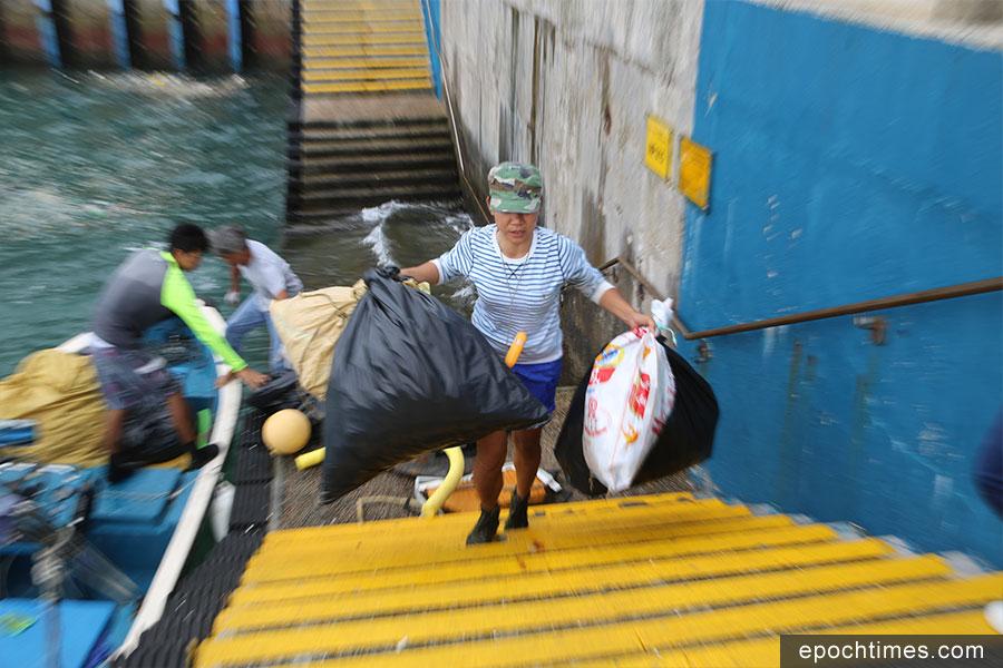 Kitti用機動艇運載垃圾到附近的碼頭,再把垃圾轉交給食環署處理。(陳仲明/大紀元)