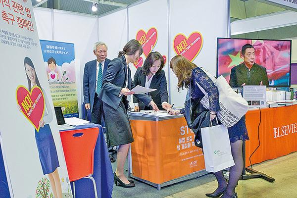 國際器官移植倫理協會會員請參加學術大會的醫療人員參加簽名活動。(全景林 /大紀元)
