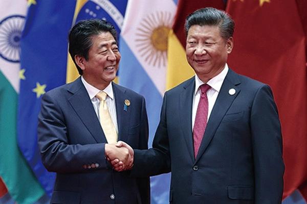 日本首相安倍晉三(左)訪華與習近平會面,雙方一改往日相見時的冰冷氣氛,皆面帶笑容。(Getty Images)