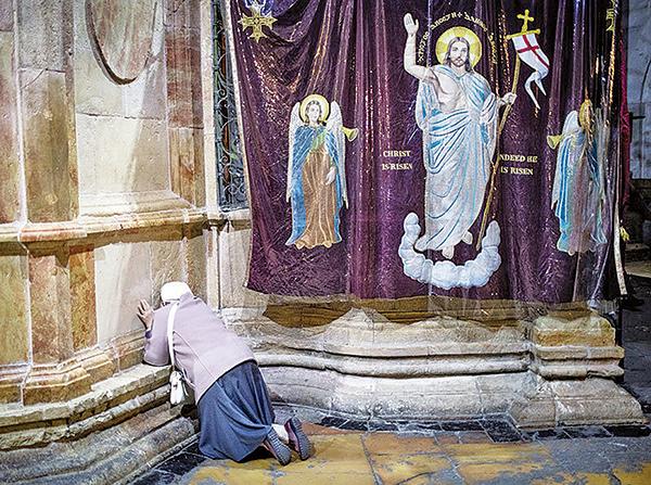 一名婦女在耶路撒冷聖墓教堂耶穌陵墓外祈禱。(Getty Images)