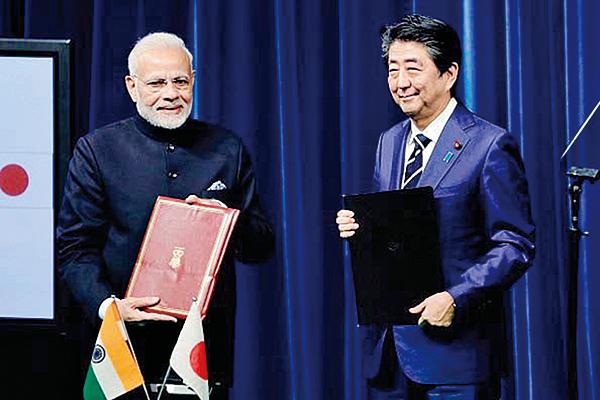圖為10月29日,莫迪(左)和安倍在東京首相官邸的記者會上,手握剛剛簽署的聯合聲明。(KIYOSHI OTA/AFP/Getty Images)