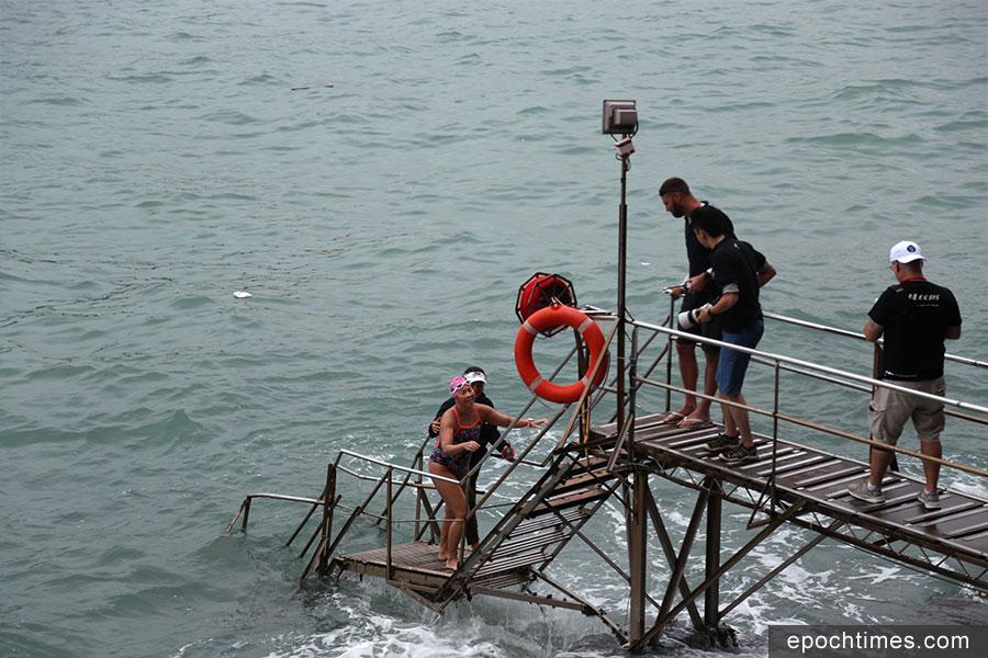 11月3日下午近5時半,Edie Hu在經歷12小時37分的挑戰旅程後,成功游泳環港島一圈,返回西環泳棚。Edie Hu在上岸的一刻,獲得在場觀眾的熱烈歡呼喝采。(陳仲明/大紀元)