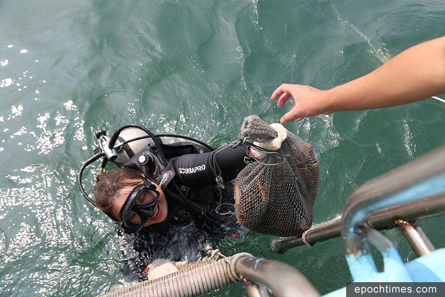 義工將海底執到的垃圾與棄置漁網帶上水面。(陳仲明/大紀元)
