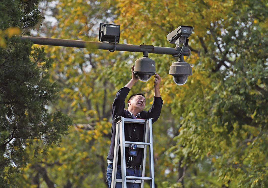 中共警方已經啟用步態識別系統,對民眾進行進一步的監控。圖為2014年9月30日,一名工人在北京天安門廣場邊緣調整監視器。(Getty Images)