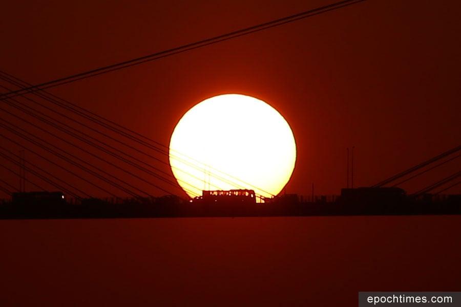 夕陽自汀九橋上徐徐落下,在穿過橋面時,大橋的鋼索和橋上的汽車在夕陽的背景襯托下,輪廓份外鮮明。(陳仲明/大紀元)