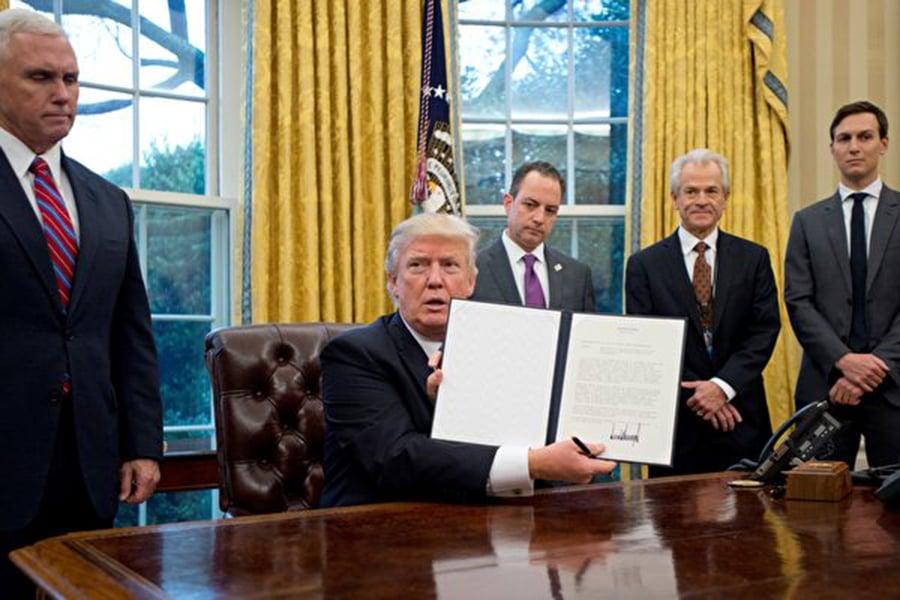 圖為美國總統特朗普簽署退出TPP的行政令。後排右二站立者是國家貿易委員會主任彼得‧納瓦羅(Peter Navarro)。(Getty Images)