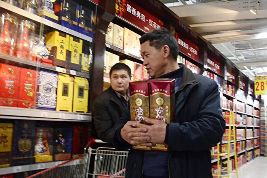 中國酒業協會發表聲明稱,白酒產品基本都含有塑化劑成分。圖為2012年11月20日一名男子在北京一家超市買了兩瓶白酒。(AFP/Getty Images)