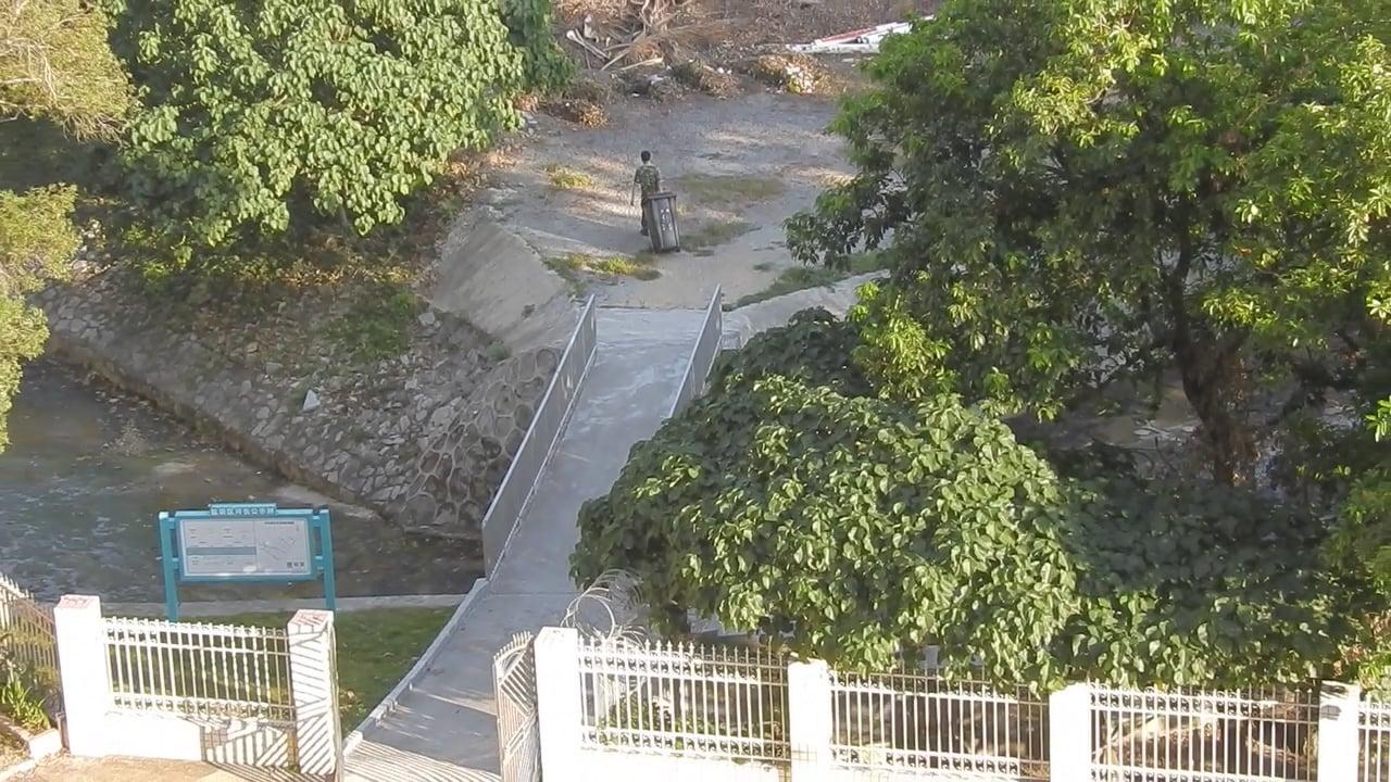 有身穿迷彩服、懷疑是部隊人員拉著垃圾桶,經過營區辦公大樓旁的石屎橋,到香港沙頭角禁區內的樹林倒垃圾。(傳真社圖片)