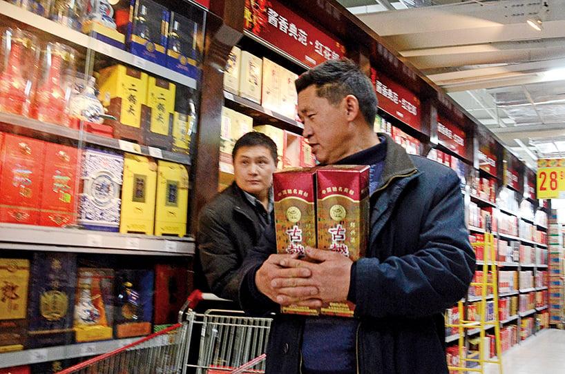 中國酒業協會發表聲明稱,白酒產品基本都含有塑化劑成份。圖為2012年11月20日一名男子在北京一家超市買了兩瓶白酒。(Getty Images)