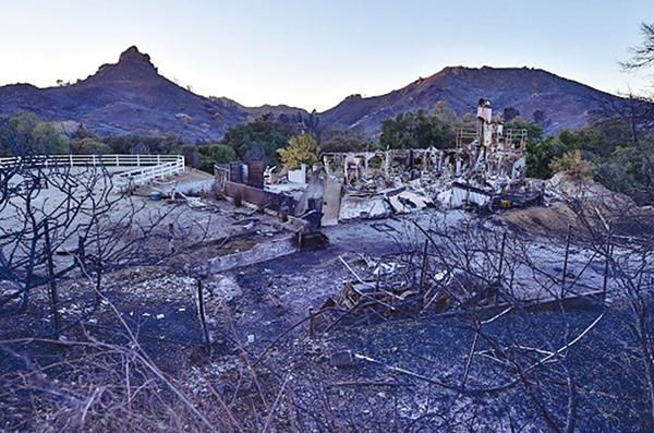 圖為2018年11月12日,在加州馬里布山上的穆赫蘭高速公路上發現一棟被「伍爾西大火」燒燬的房屋殘骸。(AFP)