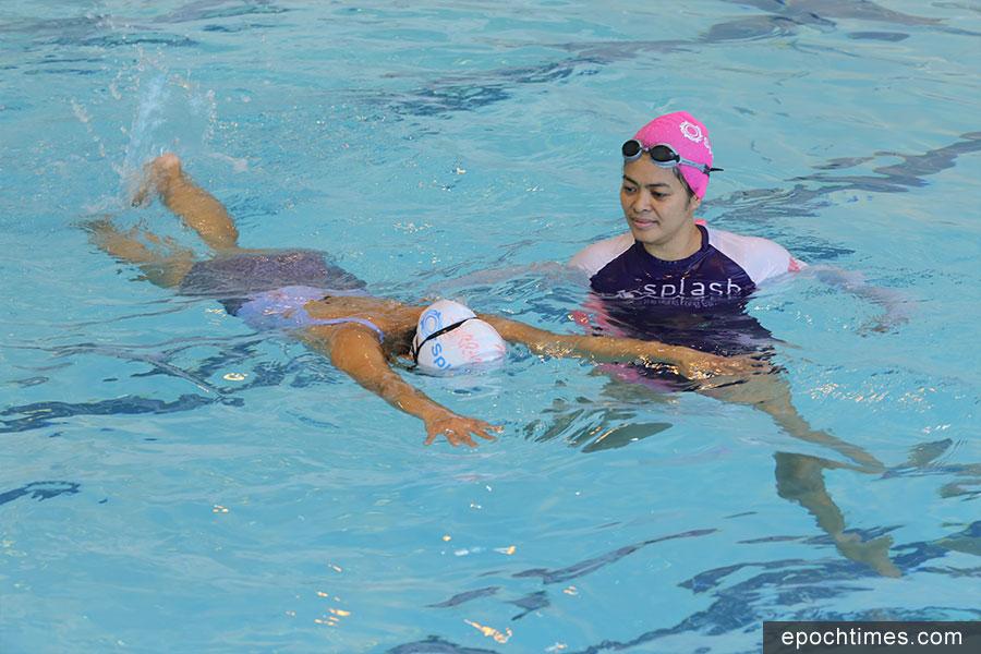 Lynly Flores(右)正在指導學員游泳技術。(陳仲明/大紀元)