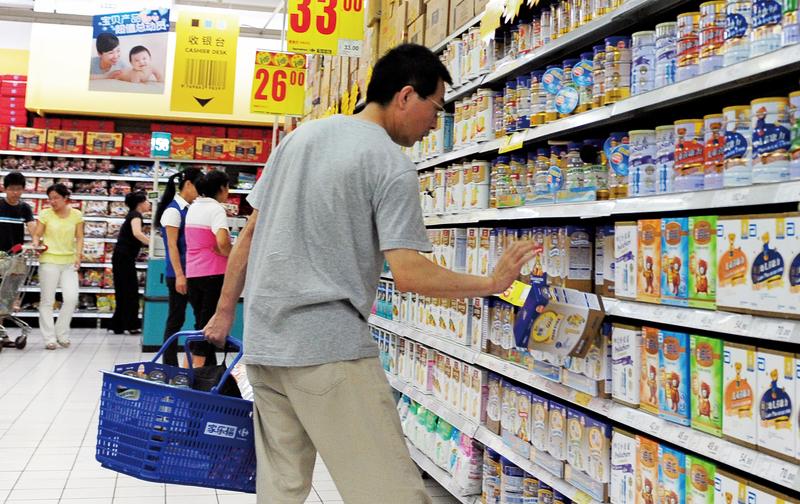 「假奶粉」屢禁不絕,不是與嚴苛的法律出台有關,而是與關部門沒真正打假有關。圖為北京一位民眾正在超市選購奶粉。(AFP)