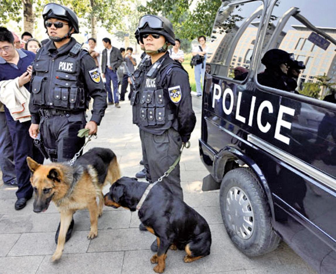 在中國國內,中共持續打壓法輪功團體。圖為全副武裝的警察帶著警犬在巡邏。資料圖(Getty Images)