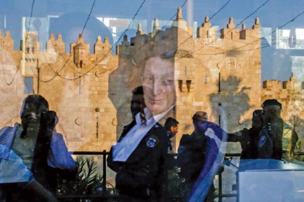 2018年5月15日,一名猶太人在耶路撒冷的公共汽車上看著車窗外的以色列安全部隊。(AFP)