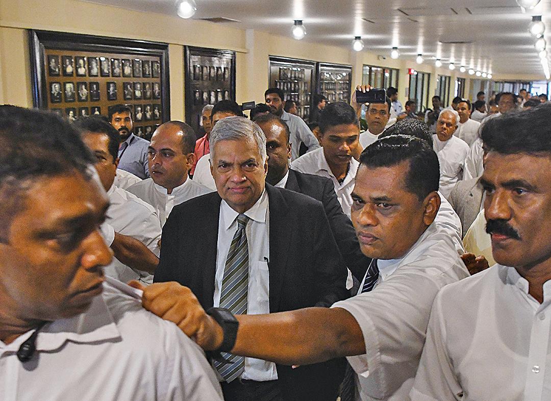 11月16日,斯里蘭卡國會再陷混亂,維克勒馬辛哈(中)由保安在周邊保護步出國會。(AFP)