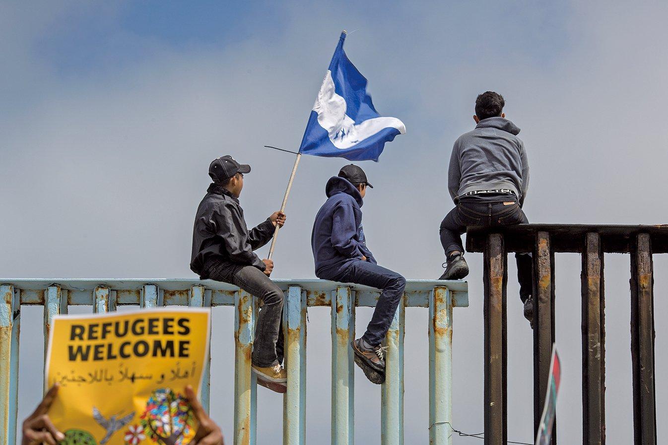圖為2018年4月29日抵達墨西哥蒂華納的前一波中美洲大篷車成員,手持洪都拉斯國旗爬上美墨邊境一處圍欄。(Getty Images)