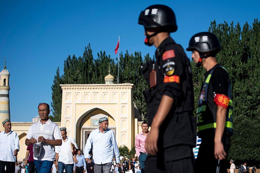 中共當局高壓管控新疆,使整個地區淪為「大監獄」。圖為2017年6月,中共警察在新疆一清真寺外。(JOHANNES EISELE/AFP/Getty Images)