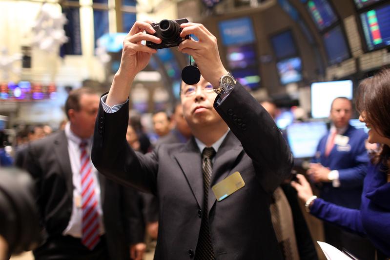 圖為2010年12月到美國上市的中國企業優酷(Youku)人員,在紐約證交所慶祝IPO拍照留念。(Spencer Platt/Getty Images)