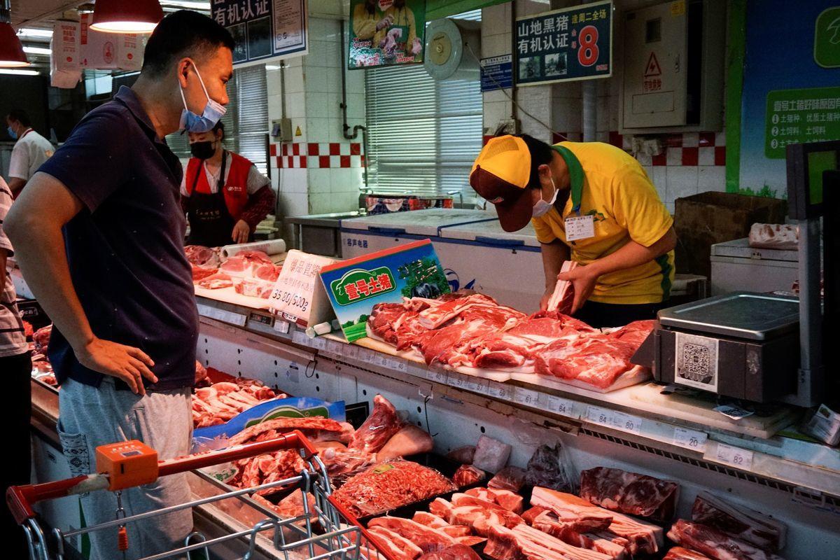 2020年6月16日,中國北京,一名戴口罩的顧客在超市買豬肉。(WANG ZHAO/AFP via Getty Images)