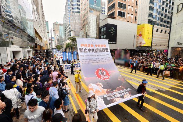 法輪功學員在香港的大遊行中曝光中共活摘法輪功學員器官的罪行。(明慧網)