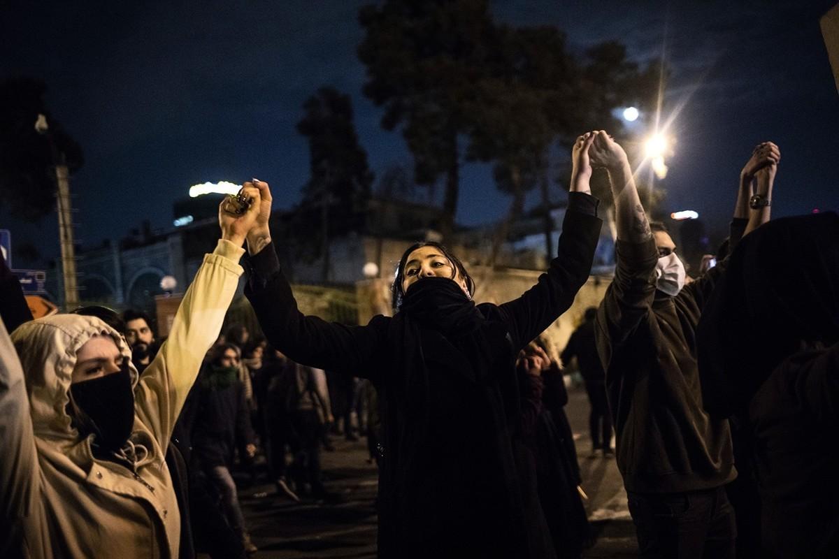 網上短片顯示,一名伊朗女子在天橋上大喊:讓哈梅內伊去死!圖為2020年1月11日,伊朗民眾在德黑蘭的一所大學前面進行抗議。(STR/AFP via Getty Images)