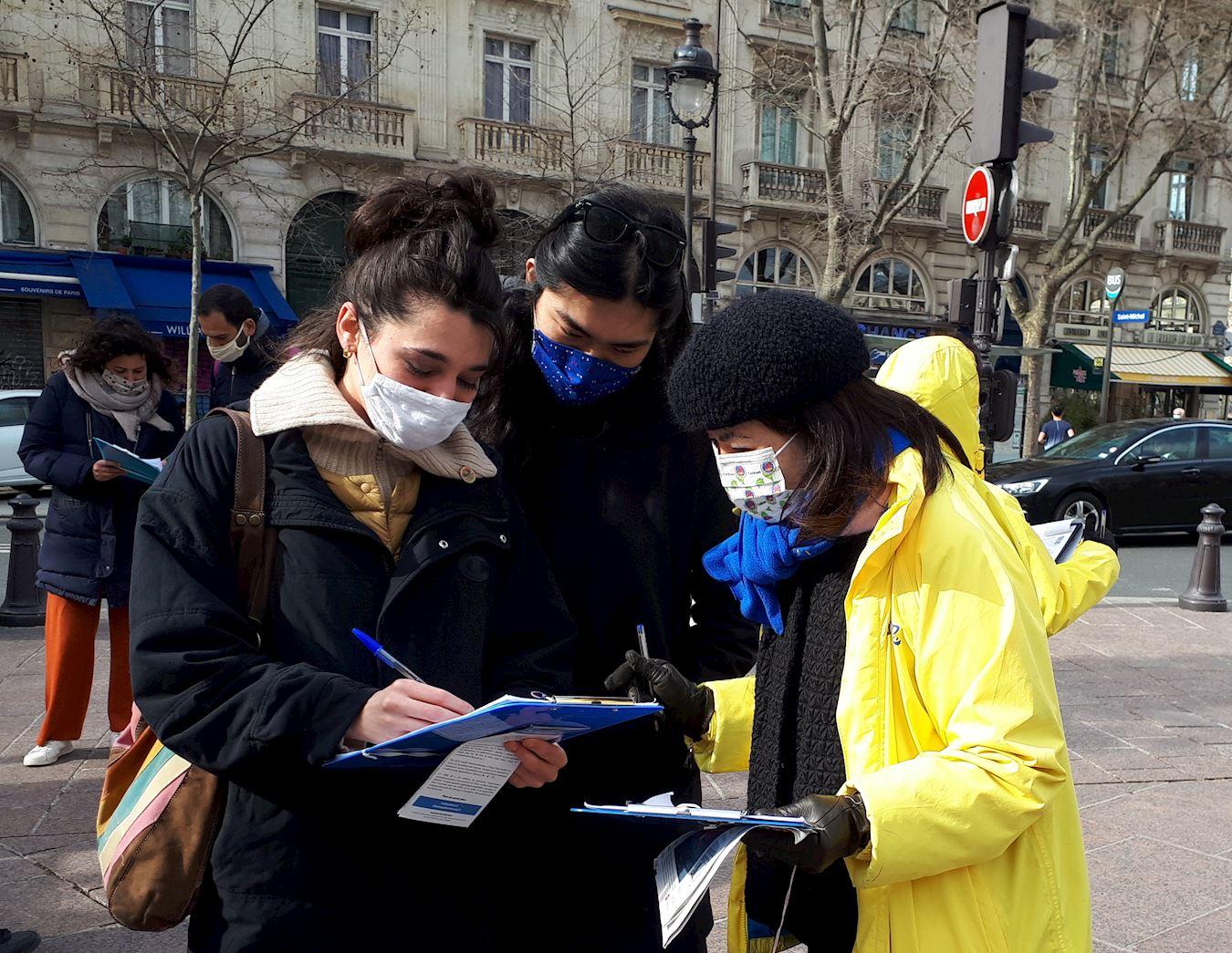 在巴黎聖米歇爾廣場上,行人簽名支持法輪功反對中共的暴行。(明慧網)