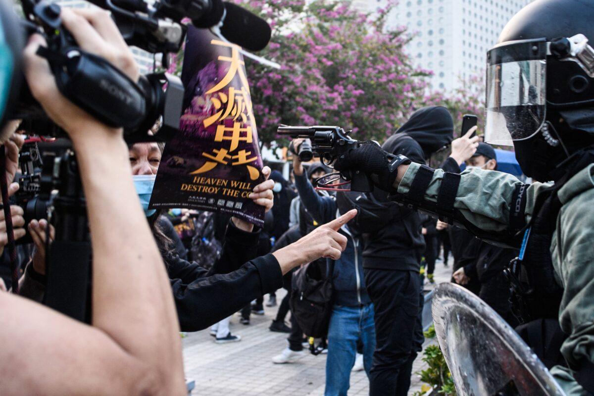2019年12月22日,在香港的一次集會上,一名警察用手槍指著抗議者。(Anthony Wallace/AFP/Getty Images)