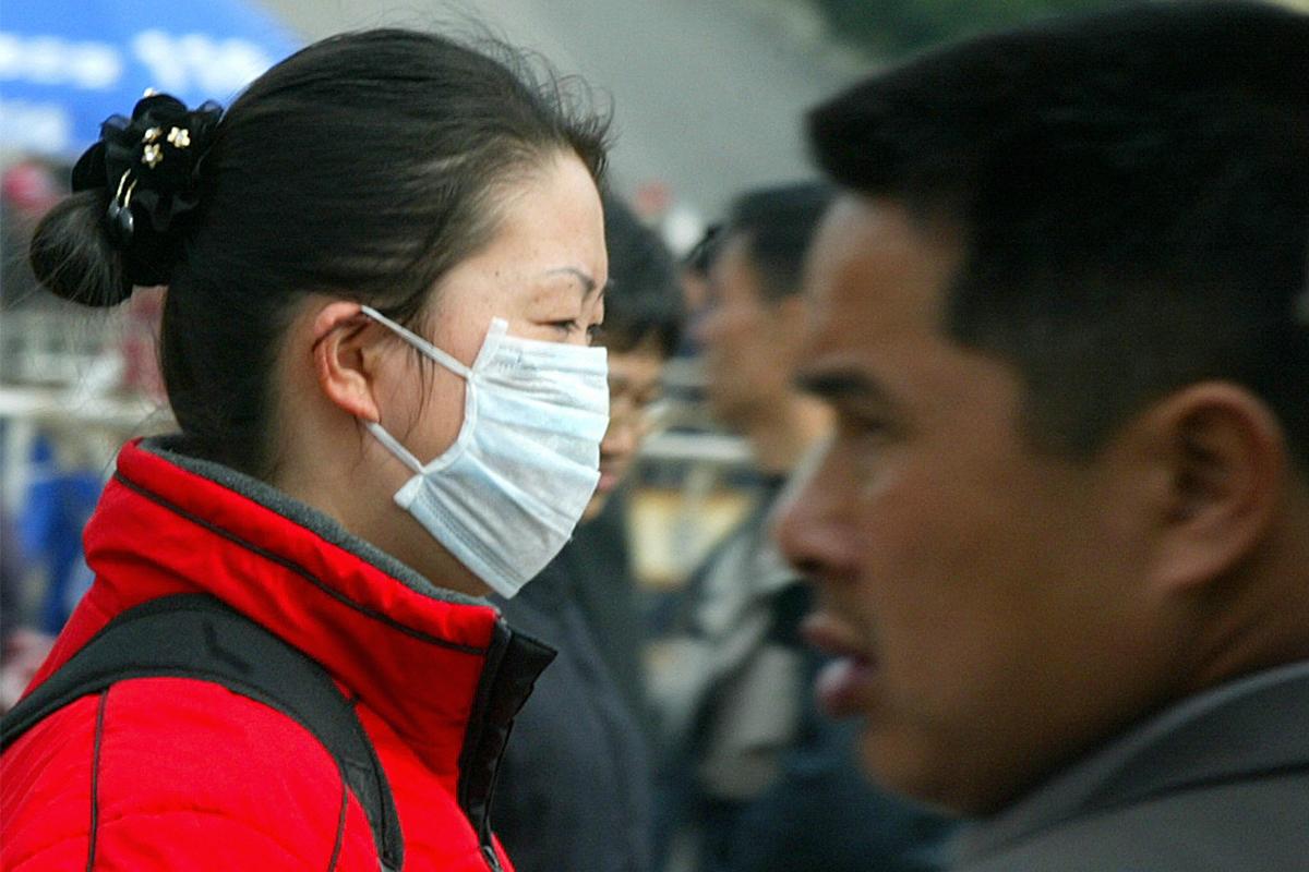 武漢爆發疑似SARS的不明病毒性肺炎。圖為2004年戴口罩預防SARS的中國民眾。(LIU JIN/AFP/Getty Images)