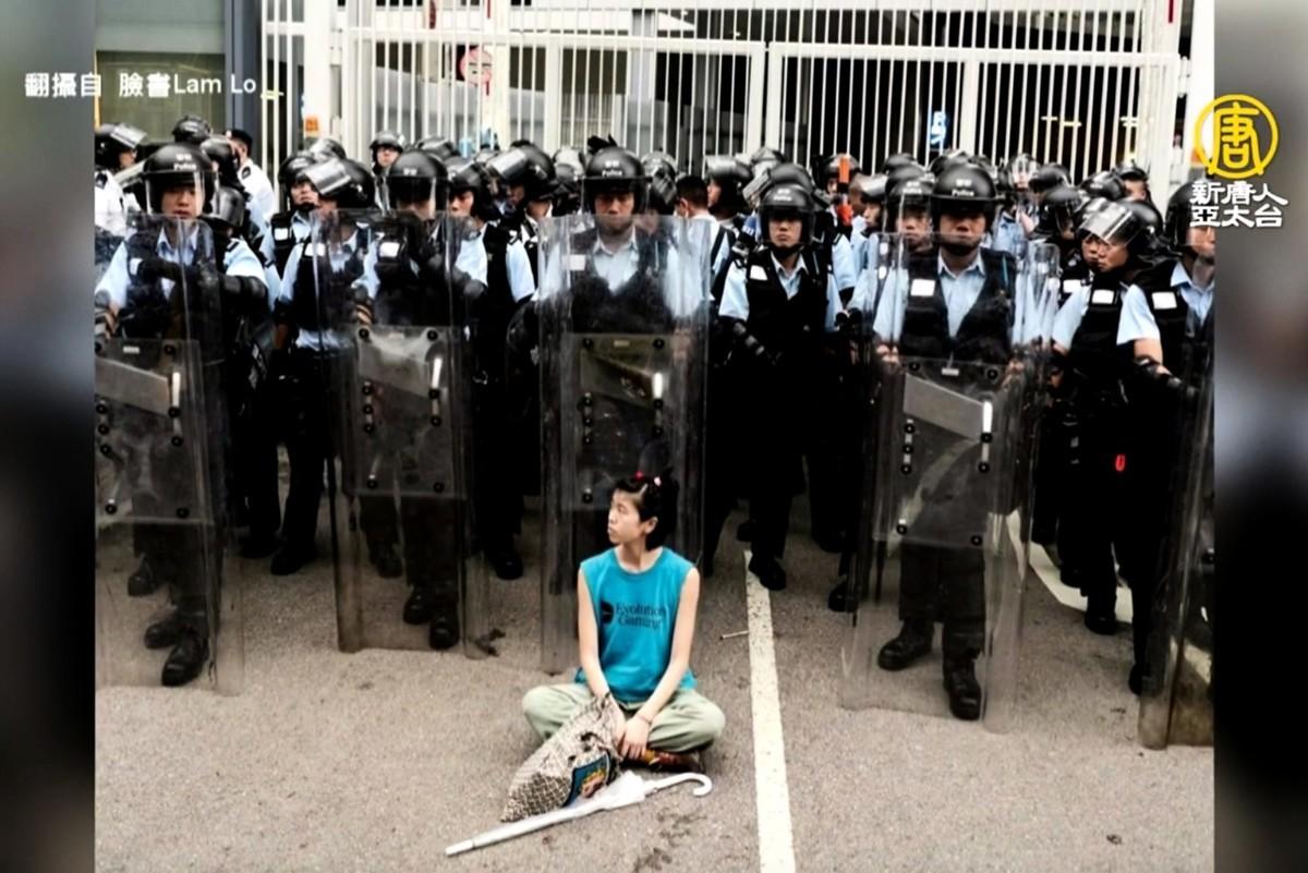 6月11日晚,在香港港府總部金鐘區,參與抗議的林嘉露在全副武裝的防暴警察前盤腿靜坐。(授權影片截圖)