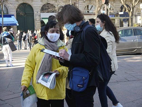 在聖米歇爾廣場,路人在徵簽表上簽字,抵制中共對法輪功的迫害。(明慧網)