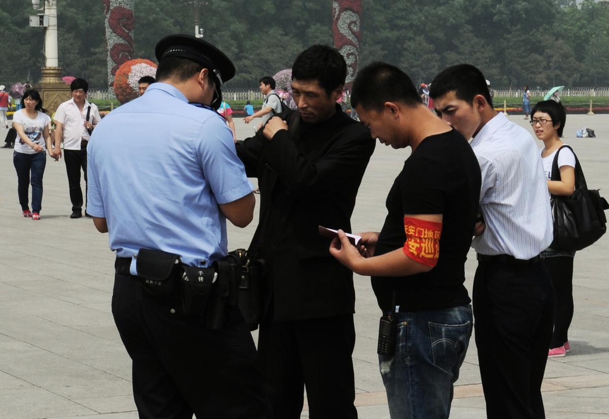 第三代身份證加入了定位及收集個人指紋和血液信息等新功能。圖為2012年中共六四屠城23周年之際,北京警察在天安門廣場檢查一名男子的身份證並逮捕了他。(AFP/GettyImages)