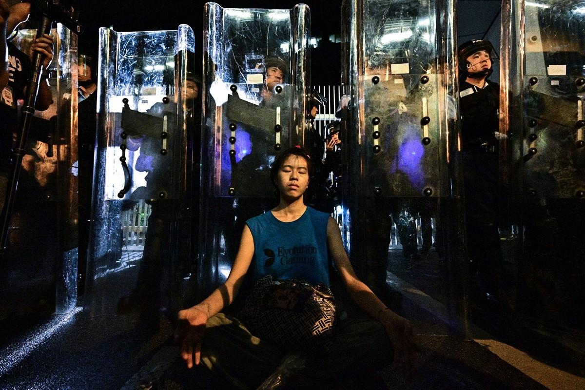 香港26歲的女孩林嘉露(Lam Ka Lo),11日晚間也前往港府總部金鐘區參與抗議,她靜坐在全副武裝的鎮暴警察盾牌前。(ANTHONY WALLACE/AFP/Getty Images)