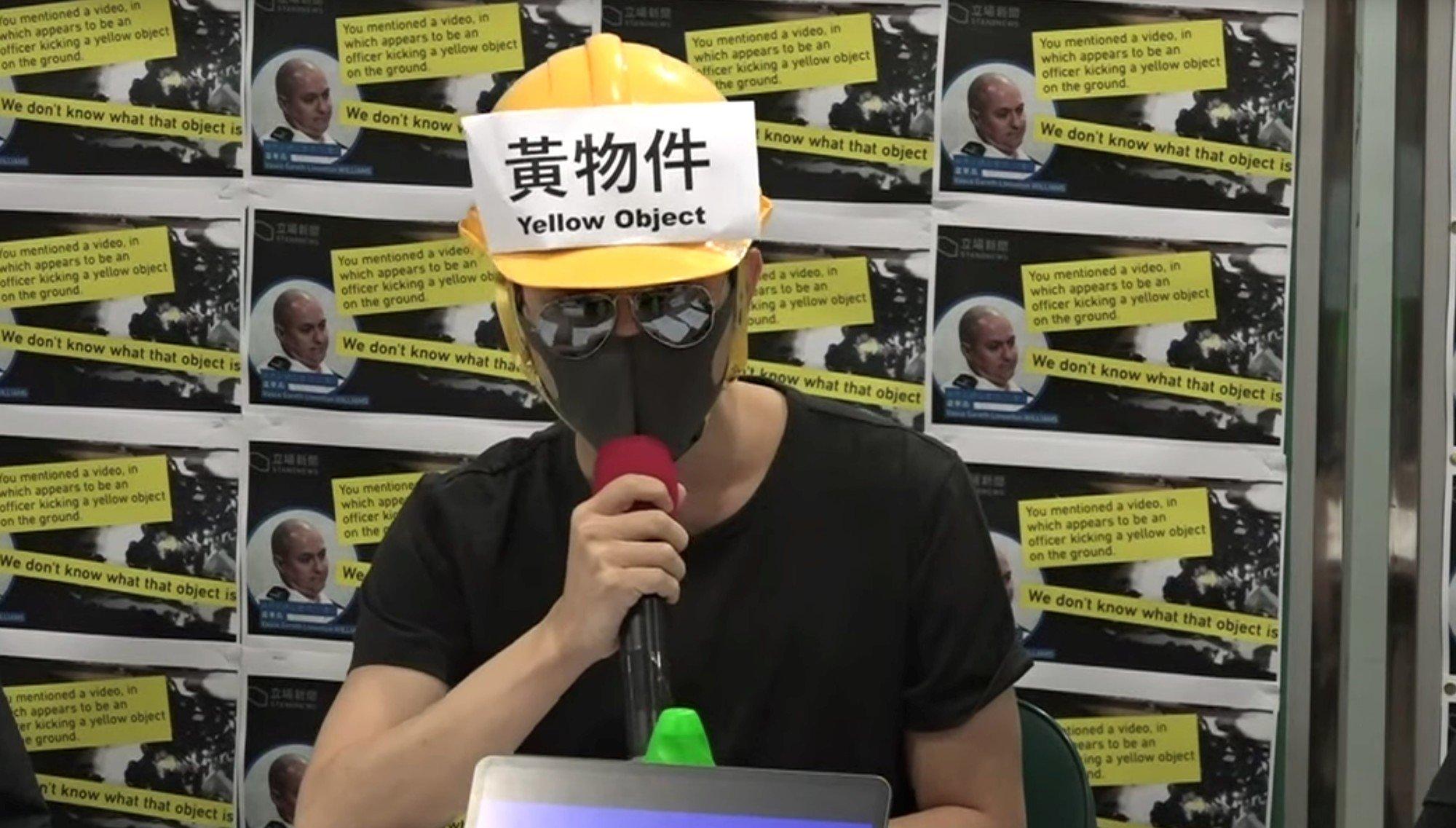 香港第14次民間記者會,發言者頭盔粘貼「黃物件」字樣,嘲諷警察。(大紀元新唐人直播畫面截圖)