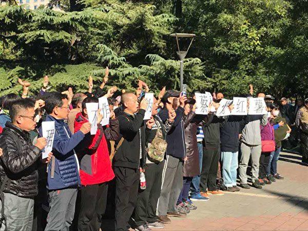 圖為10月17日,銀豆難友在東單公園,一排人手持「王珺(銀豆網案件負責人)不作為,蔡奇烤紅薯」標語,一排人手裏舉著紅薯,高呼「還我血汗錢」等口號。(受訪人提供)