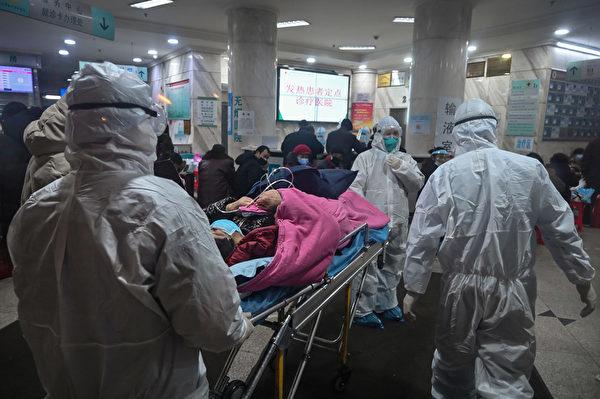 中共肺炎(俗稱武漢肺炎、新冠肺炎)遇難者家屬起訴中共政府,但遭到壓制。圖為2020年1月25日,武漢疫情嚴重時,醫療人員帶著病人到武漢紅十字會醫院。(Hector RETAMAL/AFP)