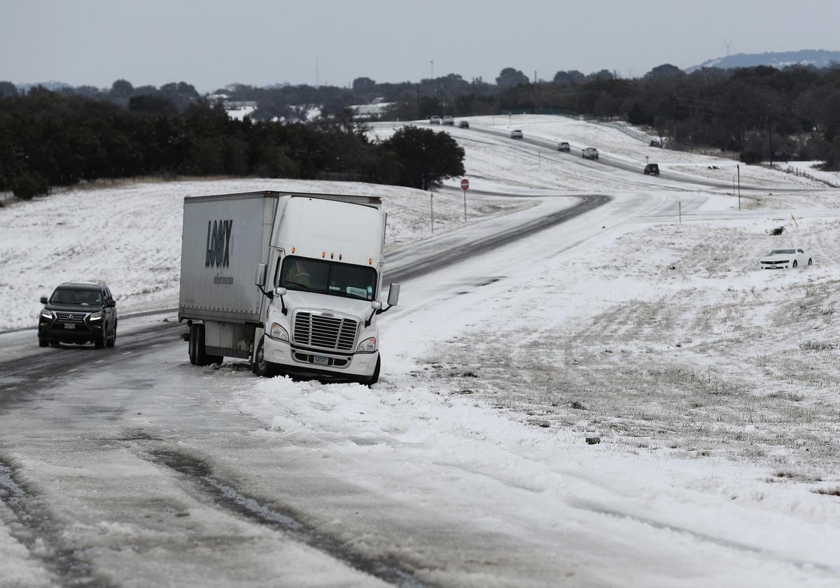 2021年2月中旬強烈暴風雪侵襲美國,一向溫暖的德州,都變成一片銀白世界。圖為2021年2月18日,德州基林,一輛貨車困在佈滿積雪的高速公路上。 (Joe Raedle/Getty Images)