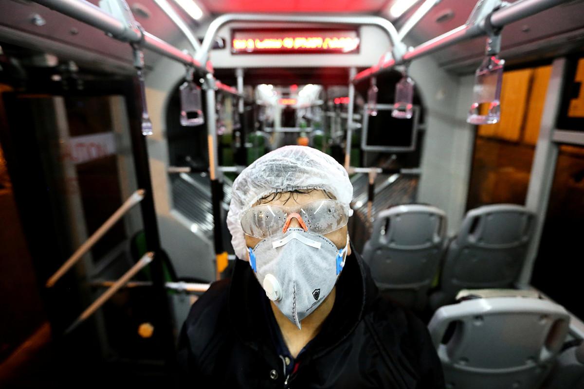 伊朗公衛系統消息人士說,截至2020年2月28日,伊朗至少有210人死於新型冠狀病毒(COVID-19)。這個數字是官方數據的6倍。圖為2月26日德黑蘭市政府一名女員工在消毒巴士。(Photo by ATTA KENARE / AFP)