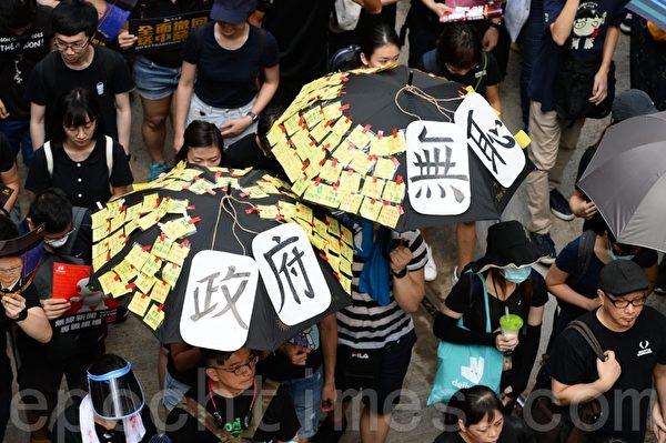 2019年7月21日,香港,民陣發起的反送中遊行隊伍中,有市民舉起掛上政府無恥紙牌和貼滿便利貼的雨傘。(宋碧龍/大紀元)