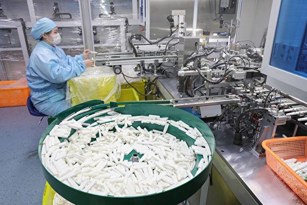 圖為江蘇一家公司的工人在生產病毒檢測盒。(STR / AFP)